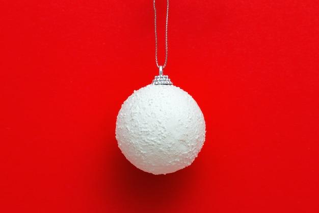 Bola de natal branco pendurada no vermelho, feriado de inverno de ano novo
