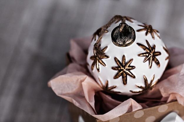 Bola de natal branco único sentado na caixa de presente