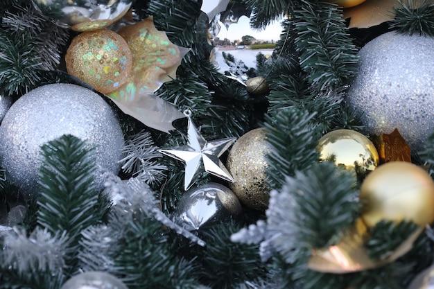Bola de natal de cor de ouro pendurar no pinheiro verde