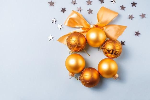 Bola de natal dourada e amarela com fita sobre fundo azul com estrelas de prata