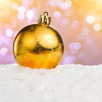 Bola de natal dourada na neve sobre fundo festivo com espaço de cópia