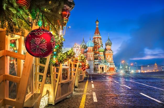 Bola de natal em ramos de abeto de casas comerciais na praça vermelha de moscou e na catedral de são basílio em uma manhã de inverno