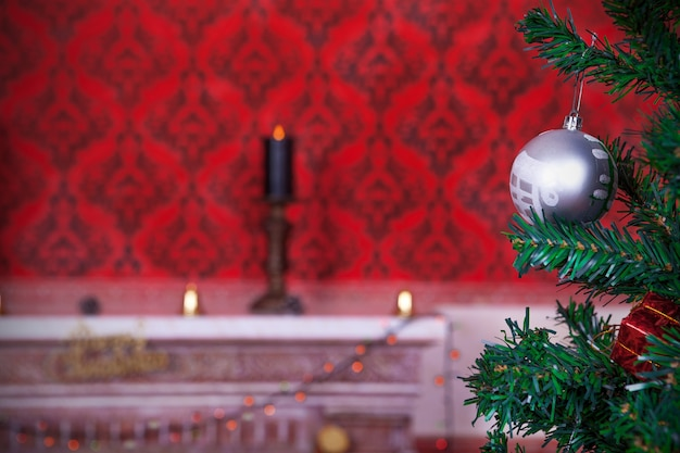 Bola de natal em um fundo vermelho vintage com uma vela acesa