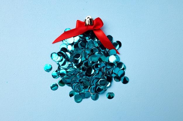 Bola de natal feita de confete em plano de fundo azul vista de cima