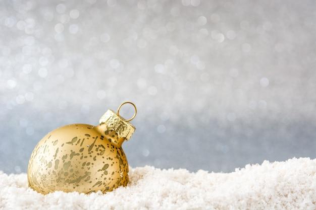 Bola de natal na superfície de neve e prata glitter
