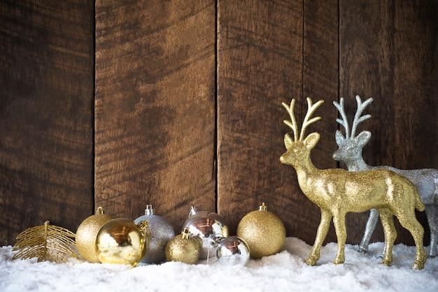 Bola de natal ouro prata e decoração de renas com fundo de madeira