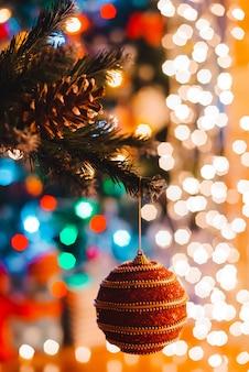 Bola de natal paira sobre um pinheiro decorado contra as luzes ardentes bokeh à noite.