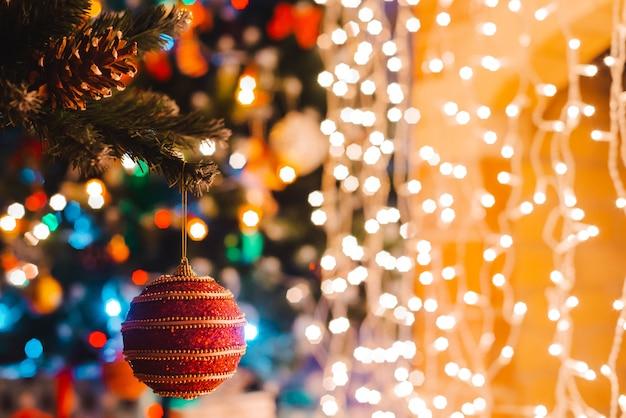 Bola de natal paira sobre um pinheiro decorado em queima luzes bokeh à noite.
