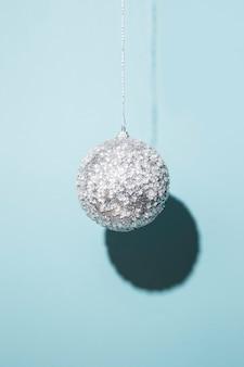 Bola de natal pendurada em um fundo azul. luz forte.