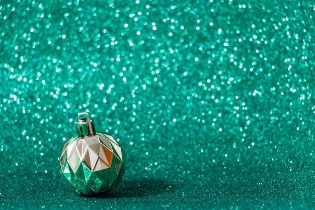 Bola de natal prateada sobre fundo verde brilhante. conceito de ano novo, cor verde maré.
