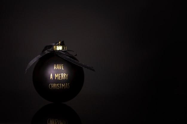 Bola de natal preta com parabéns em letras douradas sobre uma superfície preta. espaço para texto. fechar-se.