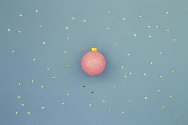 Bola de natal rosa em fundo azul com confetes de estrelas douradas