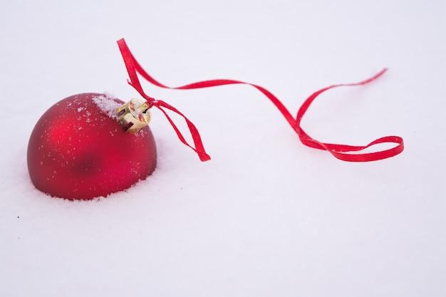 Bola de natal vermelha com uma fita vermelha na neve fofa branca.