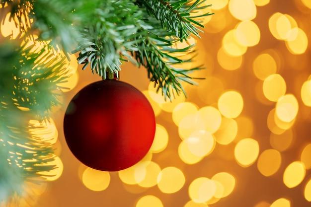 Bola de natal vermelha pendurada no galho de árvore do abeto sobre fundo dourado luzes de bokeh