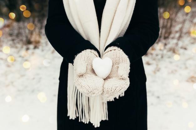 Bola de neve de coração de neve nas mãos enluvadas da garota. fundo desfocado. foto de alta qualidade