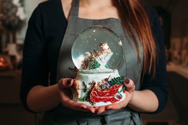Bola de neve de vidro de natal em close up de mãos femininas