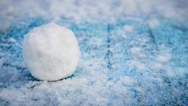 Bola de neve em uma mesa de madeira azul nevada