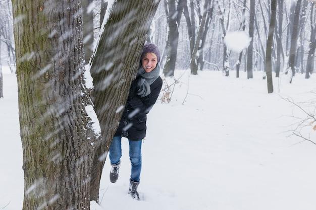 Bola de neve na frente da mulher sorridente em pé atrás da árvore