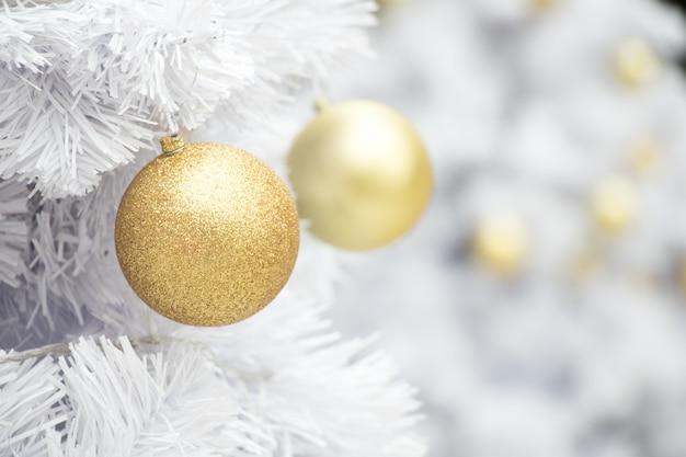 Bola de ouro no ramo branco do fundo da árvore chrismas
