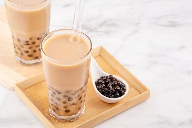 Bola de pérola de tapioca, chá com leite, bebida popular de taiwan, em copo com canudo na mesa de mármore branco e bandeja de madeira
