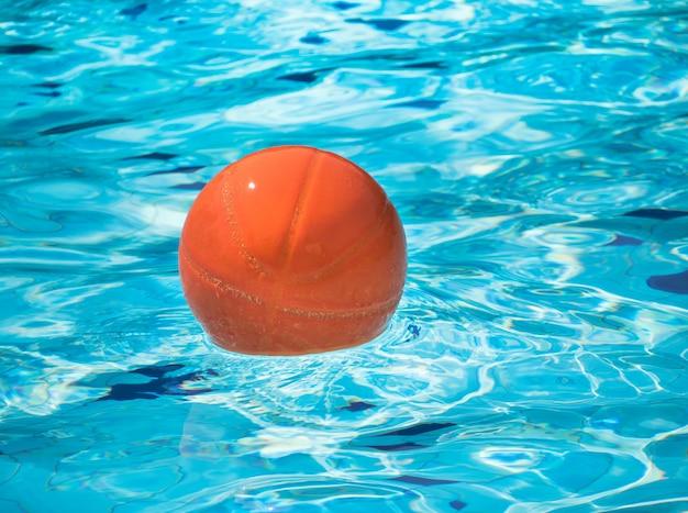 Bola de praia laranja flutuando na piscina azul.