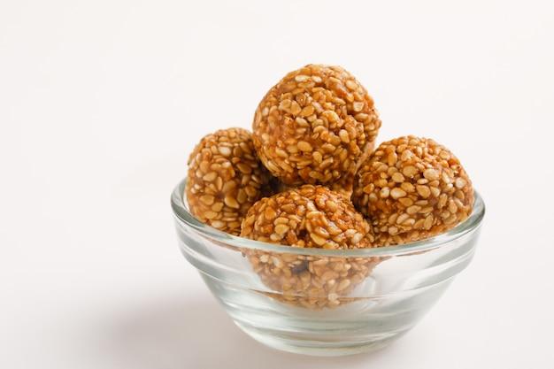 Bola de sementes de gergelim doce indiano ou chamada em hindi até ke laddu na tigela de vidro
