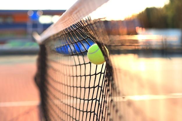 Bola de tênis amarelo esverdeado brilhante acertando a rede.