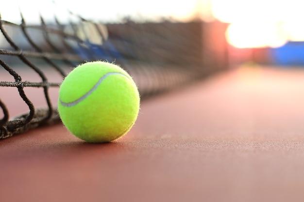 Bola de tênis amarelo esverdeado brilhante na quadra de saibro.