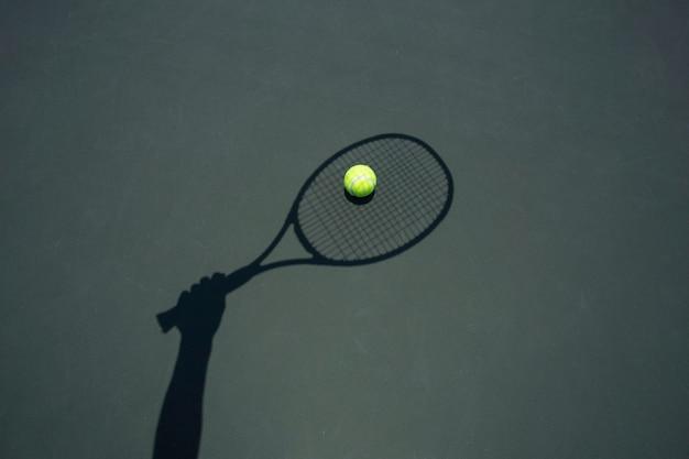 Bola de tênis com a raquete na corte de tênis.