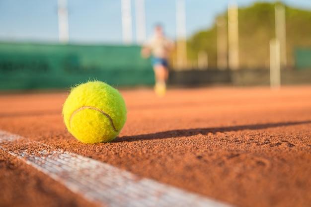 Bola de tênis, deitado na linha branca no campo de tênis em dia ensolarado.