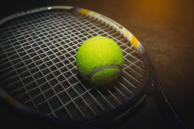 Bola de tênis e raquete na quadra dura