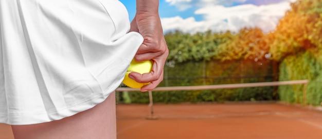 Bola de tênis na mão de uma mulher em uma saia em uma quadra de tênis. preparação para servir um balão no tênis. banner com espaço de cópia