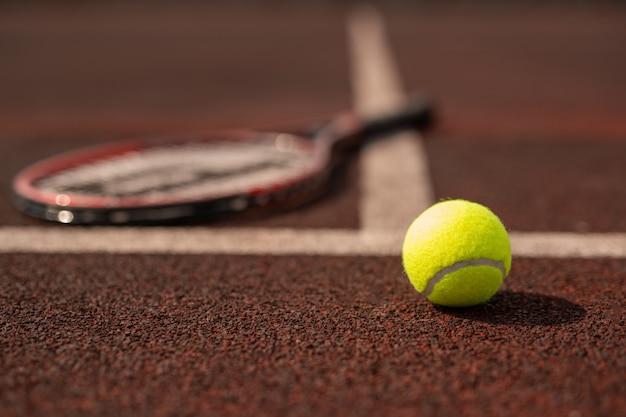 Bola de tênis no playground de esportes no estádio pela linha branca com raquete