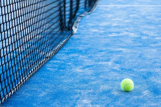 Bola de tênis ou paddle na quadra azul e rede