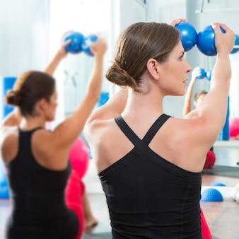 Bola de tonificação azul nas mulheres pilates classe vista traseira