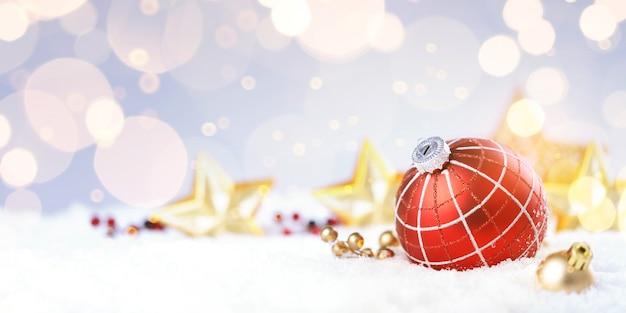 Bola decorativa vermelha na árvore de natal no bokeh de brilho com luzes douradas cintilantes.