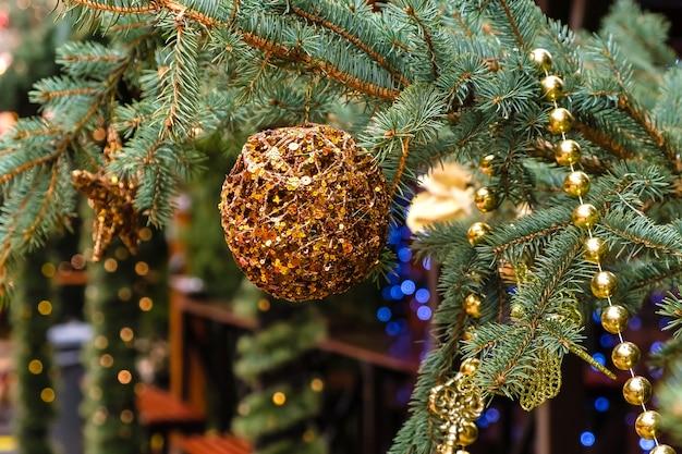 Bola dourada de natal e garland pendurada em uma árvore de ano novo
