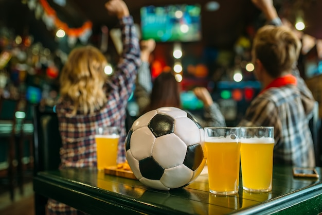 Bola e cerveja na mesa de sports bar