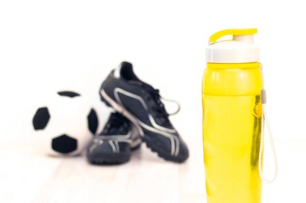 Bola e grampos, fita métrica e uma garrafa de água para escrever sobre um piso de madeira clara. preparação para a temporada de verão e praia, perda de peso e conceito esportivo