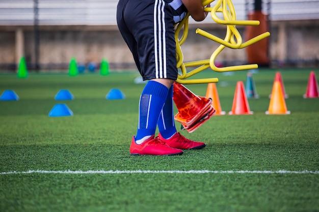 Bola infantil está coletando táticas no campo de grama com barreira para treinamento de habilidade na academia de futebol