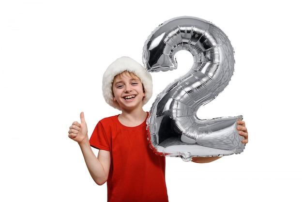 Bola inflável prata número 2 nas mãos do menino de chapéu de papai noel. .