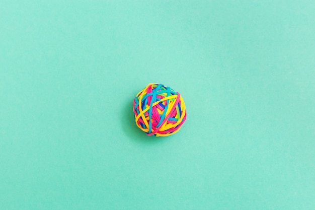 Bola ou nó de borrachas de elástico multicoloridas finas em fundo liso. emaranhado de pensamentos.