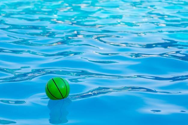 Bola verde nas águas claras da piscina. férias de verão no mar_