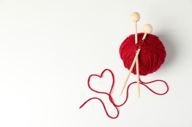 Bola vermelha de lã com agulhas de tricô em um fundo branco.