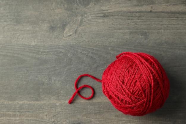 Bola vermelha de lã em fundo cinza de madeira.
