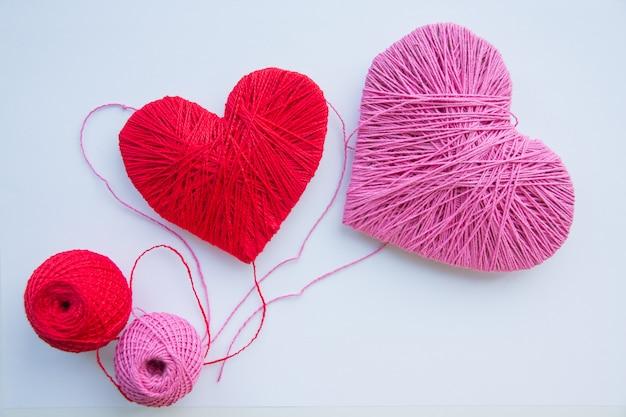 Bola vermelha de lã, fio vermelho e rosa isolado no branco