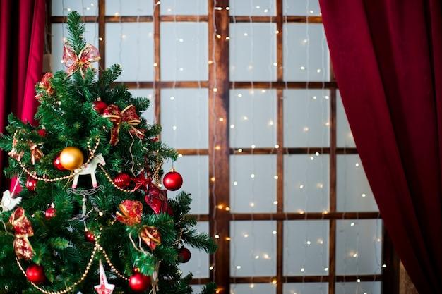 Bola vermelha de natal brilhante pendurada em galhos de pinheiro com fundo festivo