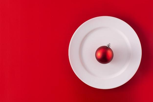 Bola vermelha de natal na chapa branca. conceito de jantar de natal.
