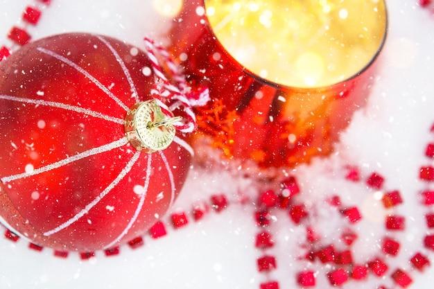 Bola vermelha de natal na neve branca natural com miçangas quadradas e vela acesa em um castiçal de vidro. natal, ano novo ao ar livre. queda de neve, clima festivo de contos de fadas e magia, decoração de rua.