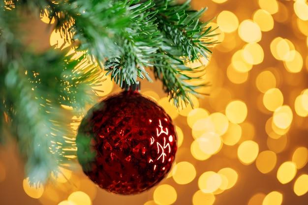 Bola vermelha de natal pendurado no galho de árvore do abeto sobre luzes de fundo dourado bokeh